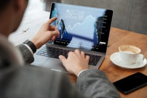 image-recadree-homme-affaires-assis-pres-table-dans-cafe-analyse-indicateurs-ordinateur-portable_171337-5598